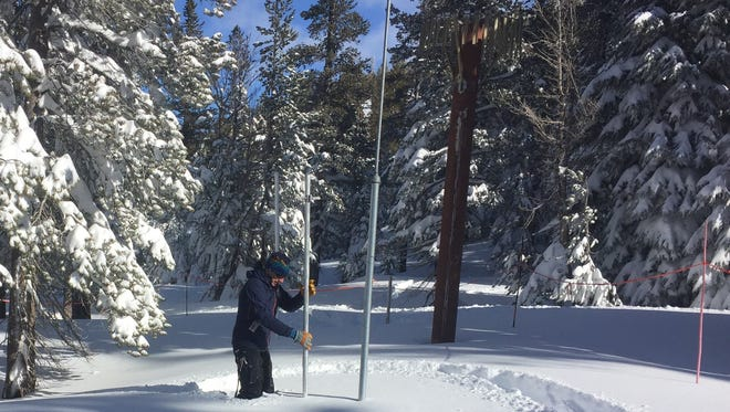 Hydrologist Jeff Anderson of the Nevada Natural Resources Conservation Service uses an aluminum tube to measure snow at Mt. Rose Ski Tahoe on Slide Mountain near Reno, Nev., on Jan. 5, 2017.