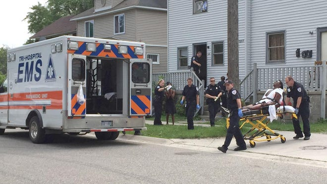 A victim is wheeled to the ambulance by EMS workers Thursday in the 1200 9th Street in Port Huron.