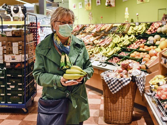 A woman buys fruits at a supermarket in Bergisch Gladbach that is open in the morning only for elderly people from 65 years to minimize their risk of infection due to the coronavirus outbreak in Germany, Friday, March 20, 2020. For most people, the new coronavirus causes only mild or moderate symptoms, such as fever and cough. For some, especially older adults and people with existing health problems, it can cause more severe illness, including pneumonia. (AP Photo/Martin Meissner)