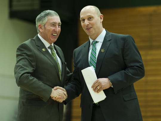 UVM's new athletic director Jeff Schulman shakes hands with retiring AD Bob Corran during the announcement ceremony at Patrick Gym on Wednesday in Burlington.