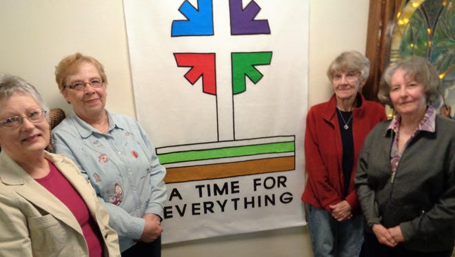 Rebecca Circle members, from left, Joan Muss, Barbara Rader,  Sigrid Bensen and Anita Roggenbaum. They make banners to decorate the church, including this one to commemorate Pentecost.