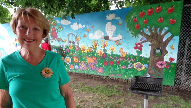 Marylou Rutkowski with a mural painted by local children that decorates the walls of Sunflower Park in Binghamton's First Ward.