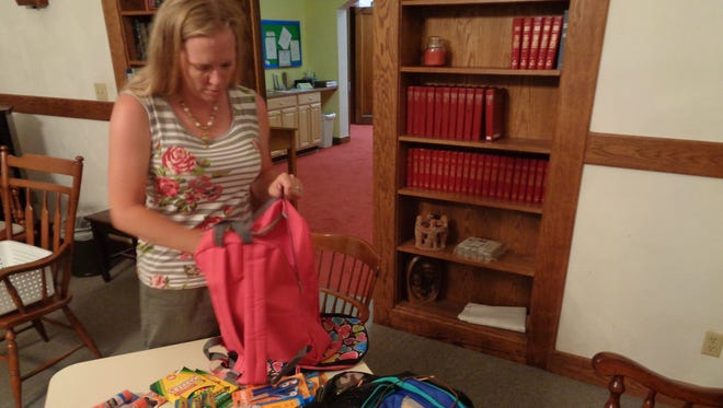 Kelly Crane, who coordinates the annual backpack drive at Central United Methodist Church of Endicott, packs a backpack. Church members collect school supplies and backpacks for children who need them and will give them away on Sunday.