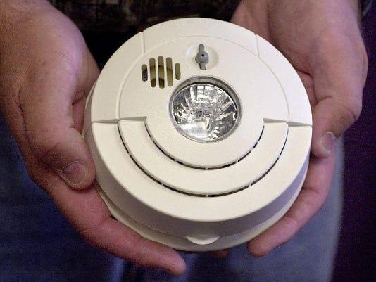holding smoke alarm