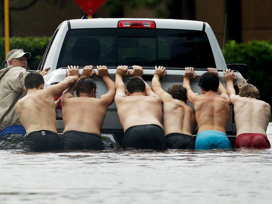 A group of people push a stalled pickup through a flooded