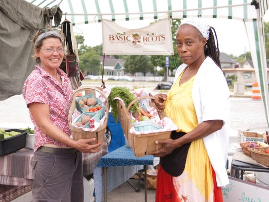 """Kay Grimm and Camille Steward (left to right) run Basic Roots Community Foods.  All of their foods are grown in Indianapolis.  Their motto is  """"Making good food accessible."""""""
