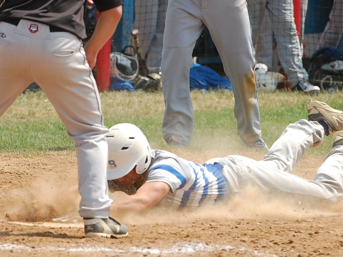 Alex Popovich of Northern Burlington slides safely in with a run during the fifth inning of Saturday's game.