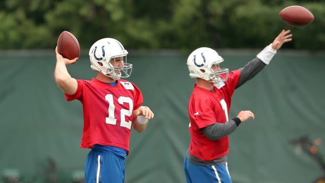 Colts quarterbacks Andrew Luck and Bryan Bennett warm-up at the start of practice at the Colts training facility on Wednesday, June 3, 2015.