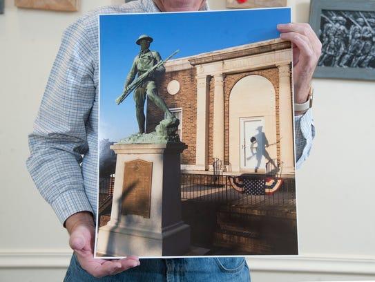 Erik Burro holds his photo of a Burlington City World