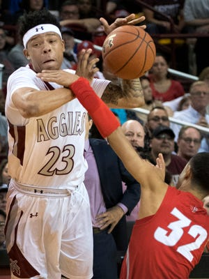 New Mexico State's Zach Lofton tries to push the ball up court and is fouled by New Mexico's Anthony Mathis during second half action Friday night at the Pan American Center.