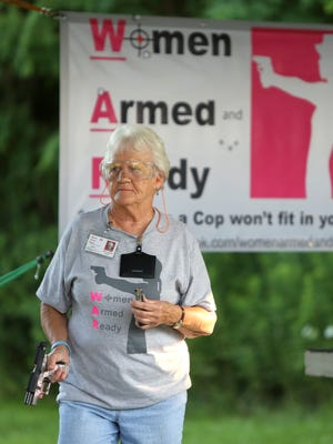 """Addie VanWinkle, 78, of Aurora gets ready for target practice in Versailles. """"I hope I never have to use it,"""" the Women Armed and Ready member says."""