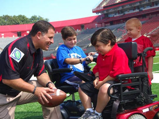 In 2011, Rutgers football coach Greg Schiano greets Danny Garofalo (foreground, in red).
