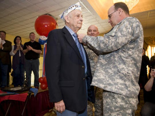 Army veteran Arthur Seltzer receives Bronze Star for service in the Battle of the Bulge in World War II from Army Col. Jeffrey Doll at Joint Base McGuire-Dix-Lakehurst in 2012.