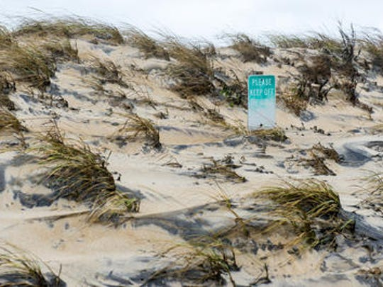"A ""Please Keep Off The Dunes"" sign in South Bethany is almost swallowed by sand following storms over the weekend on Monday afternoon."