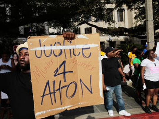A man holds a sign expressing himself during a protest
