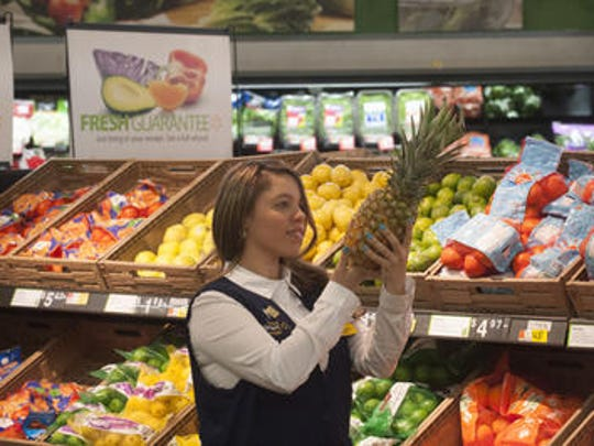 Esther Moralez Ortez, a Walmart employee, carries fruit in the store. Ortez graduated from the newly-opened training academy at the Williamstown store on Thursday morning. She's worked at the store for a year after transferring from Puerto Rico.