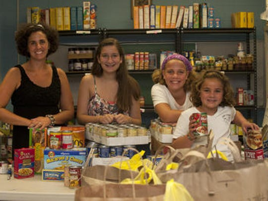 Moorestown's Kahra Buss (left), Alexis Angelini, Grace Buss and Abigail Buss are shown working at food pantry for their nonprofit Live Civilly at the St. Matthew Lutheran Church in Moorestown. Kahra Buss was named the new executive director at Perkins Center for the Arts.