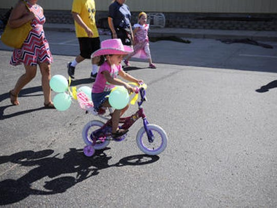 Parade participants fly by on scooters, wagons and bikes as part of the kiddie parade in August 2015.