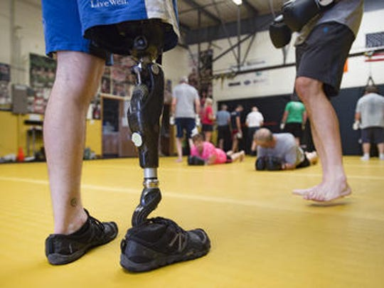 Rustin Hughes trains a group during a Rock Steady Boxing class for people with Parkinson's at Trials Martial Arts on Wednesday, August 2, 2017. Hughes, who lost his right leg three years ago has been using a special socket on his prosthetic leg from Windsor-based Quorum Prosthetics.
