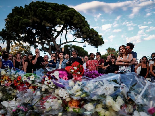 People gather in front of the memorial set on the 'Promenade