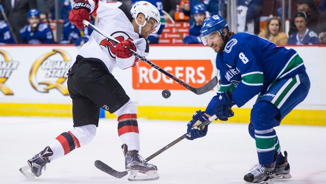 New Jersey Devils' Taylor Hall, left, has his shot blocked by Vancouver Canucks' Chris Tanev during the first period of an NHL hockey game, Wednesday, Nov. 1, 2017 in Vancouver, British Columbia.   (Darryl Dyck/The Canadian Press via AP)