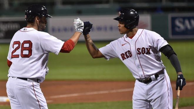 Yairo Munoz, right, congratulates Red Sox teammate J.D. Martinez on hitting a home run on Saturday night.