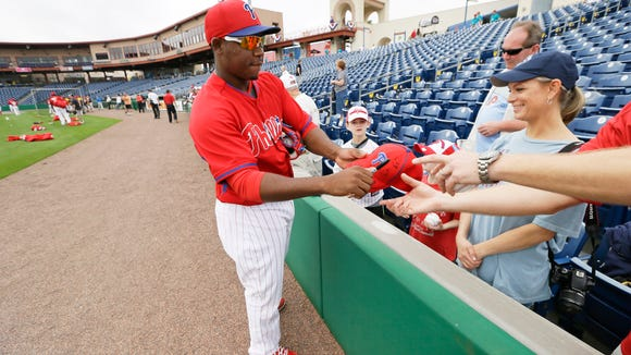 Philadelphia Phillies third baseman Maikel Franco signs autographs before an exhibition baseball game against the Toronto Blue Jays Wednesday, Feb. 26, 2014, in Clearwater, Fla. (AP Photo/Charlie Neibergall)
