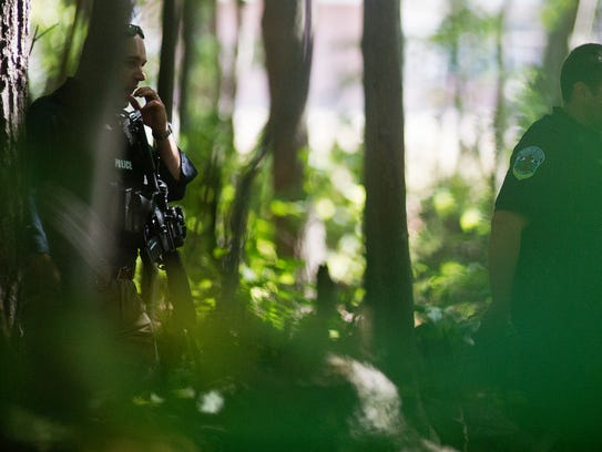 Burlington police officers guard a wooded area between