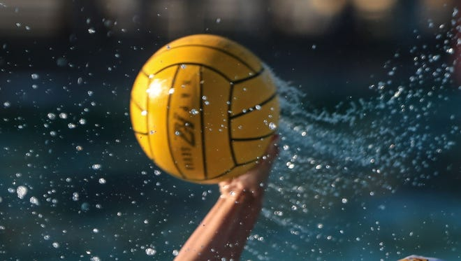 FILE - A water polo player attempts a shot at net.