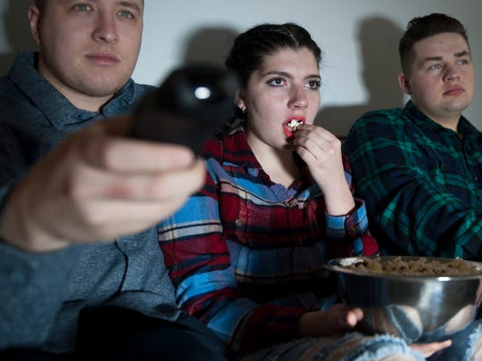 Rowan University students, from left, Ryan Klohr, Lauren Bitzer, and Rob O'Leary watch an episode of Black Mirror at O'Leary's Glassboro apartment.