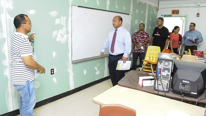 Assistant Principal John Castro, left, explains the repair work done to a wall in a Chamorro classroom to Guam Department of Education Superintendent Jon Fernandez during an inspection tour at C.L. Taitano Elementary School in Sinajana on Tuesday, July 28. Superintendent Jon Fernandez, center, on Tuesday continued his site inspection of school campuses.