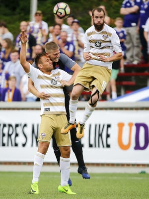 FC Cincinnati defender Harrison Delbridge (4), center, is challenged by Louisville City FC midfielders Niall McCabe (11), left, and Brian Ownby (10), right, in the first half during the Lamar Hunt US Open Cup game between Louisville City FC and FC Cincinnati Wednesday at Nippert Stadium.