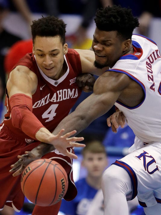 Kansas center Udoka Azubuike (35) and Oklahoma center Jamuni McNeace (4) reach for a loose ball during the first half of an NCAA college basketball game in Lawrence, Kan., Monday, Feb. 19, 2018. (AP Photo/Orlin Wagner)