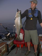 Case Christensen of Manitowoc admires a Chinook salmon caught at sunset on a recent Sunday.
