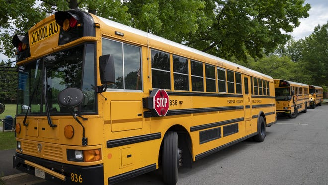 Fairfax County Public School buses set idle at a middle school in Falls Church, Va., Monday, July 20, 2020, as the nation's 10th largest school district moves forward with plans that allow students to receive two days a week of in-person instruction when classes start during the Covid-19 pandemic.