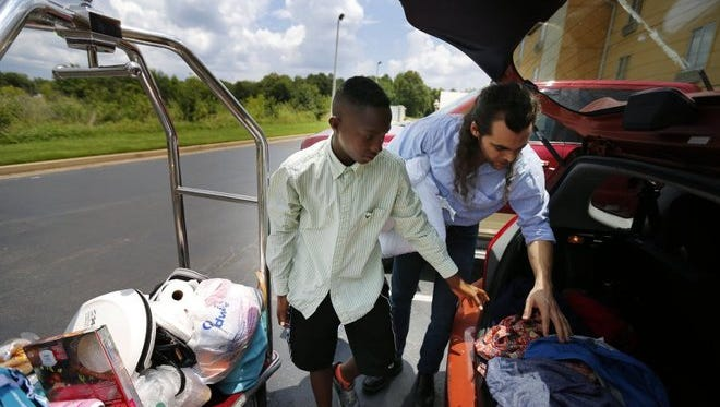Chauncy Black, 15, (left) helps load his and his family's belongings into Matt White's car outside a hotel Sunday. A campaign started by White to raise $250 to purchase a lawn mower for Black to earn money has garnered more than $250,000 in donations, and the money keeps coming in.