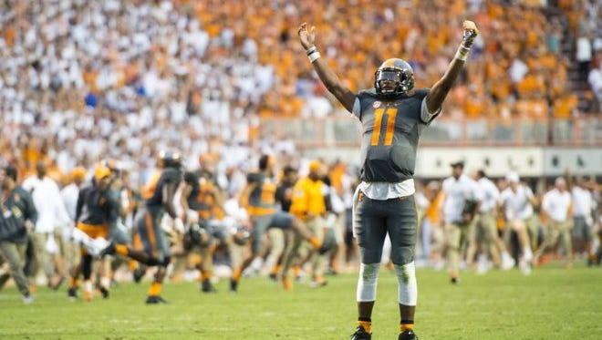 Tennessee quarterback Joshua Dobbs raises his arms in victory after the Vols beat Florida 38-28 on Saturday at Neyland Stadium, ending an 11-game losing streak to the Gators.
