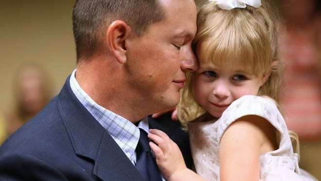 Steve Reaves holds his daughter Bella Grace Reaves, 3, during the finalization of her adoption on Nov. 20, 2015, in County Court-at-Law No. 5. Five families had their adoptions approved during the adoption day event.