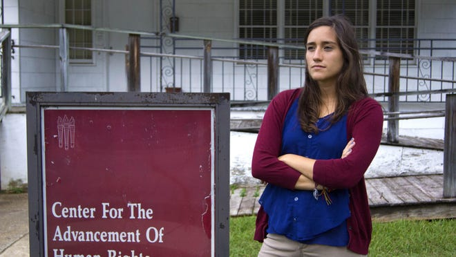 """Daniela Donoso Garcia stands by the sign for the """"Center for the Advancement of Human Rights."""""""