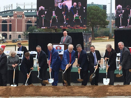 Baseball Commissioner Rob Manfred, fourth from left, and team owners Bob Simpson, sixth from left, and Ray Davi along with other dignitaries participate in a groundbreaking ceremony outside Globe Life Park, seen in background, Thursday, Sept. 28, 2017, in Arlington, Texas. The ceremony was for the team's $1.1 billion retractable-roof stadium that is scheduled to open in time for the 2020 season. (AP Photo/Stephen Hawkins)