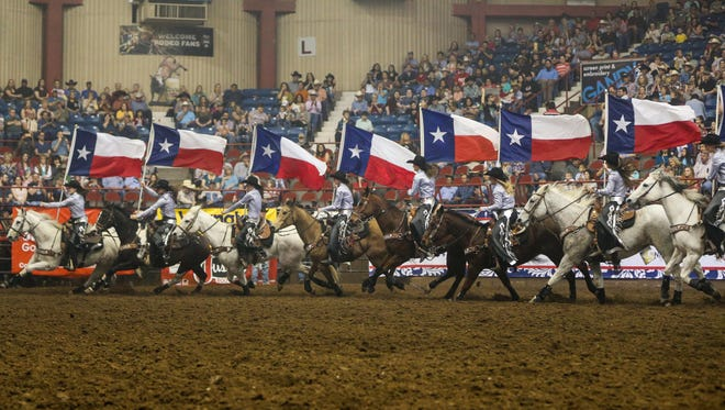 The Rodeo Ambassadors ride into Foster Communications Coliseum with Texas flags during a San Angelo Stock Show & Rodeo performance.