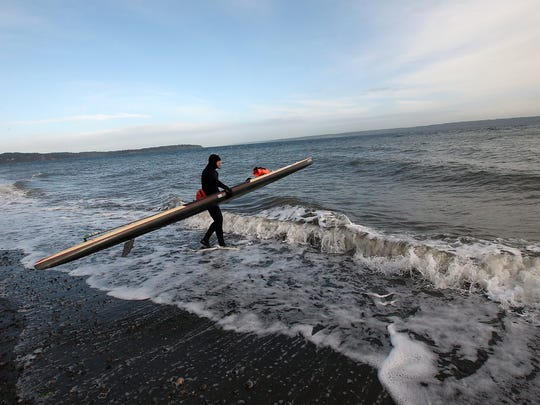 Steve Rhoades walks into the surf with his paddleboard at Bainbridge Island's Fay Bainbridge park on Thursday, Jan. 18, 2018. Rhoades will by paddling from Bainbridge to Port Townsend to Ketchikan, Alaska, and then riding 4,800 miles on his bicycle this summer, all as a fundraiser for the homeless. Rhoades was once an addict and was himself homeless for 15 years but now runs an organization called Extreme Sobriety, which provides support and training for the homeless, addicts and others.