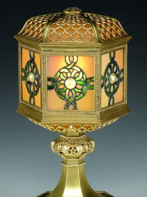 "This 15 1/2-inch-tall table lantern marked ""Tiffany Studios New York"" sold for $6,655 at a recent James D. Julia auction in Maine. It has a shade with glass panels centered with a cabochon jewel. The stem is decorated bronze with a gold patina."