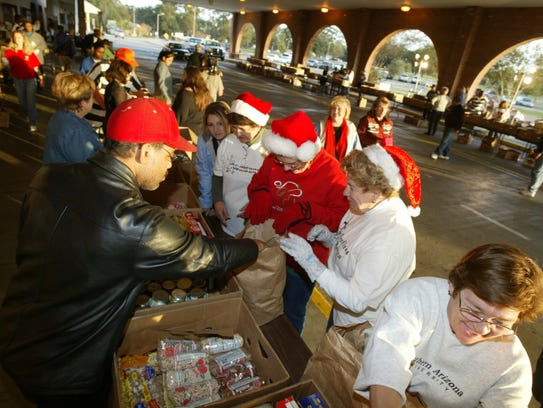 Dozens of volunteers sort food donated by the public