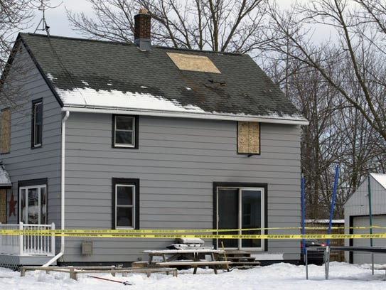 Windows and part of a roof are boarded up following
