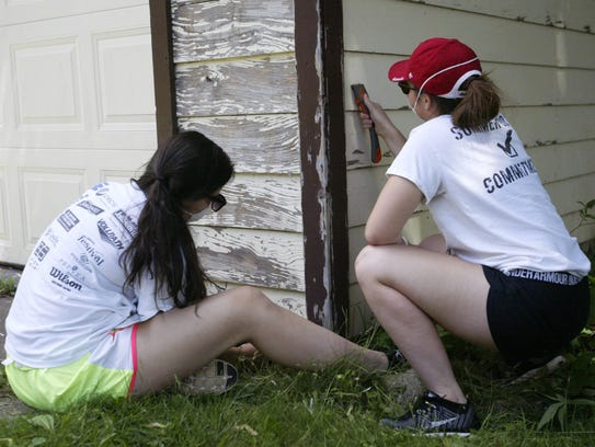 Amy Pfile, left, and Caitlyn Cobb chip old paint off