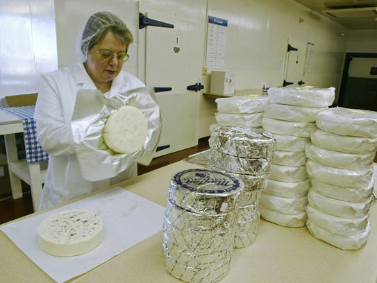 A worker wraps 2-pound wheels of Maytag Blue Cheese