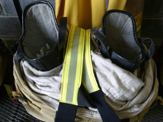 A pair of firefighters' boots sits on the floor of