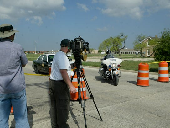 Media stand outside the barricades as San Angelo police