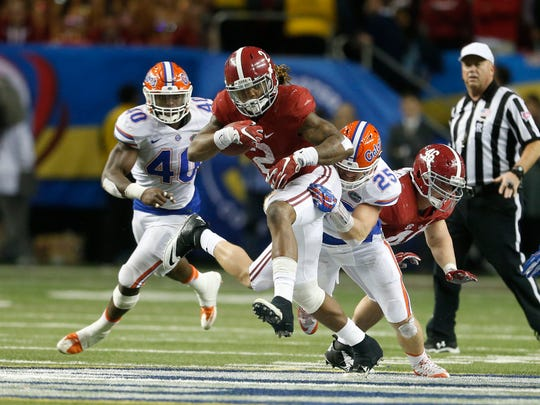 Dec 5, 2015; Atlanta, GA, USA; Alabama Crimson Tide running back Derrick Henry (2) carries the ball defended by Florida Gators linebacker Matt Rolin (25) during the fourth quarter in the 2015 SEC Championship Game at the Georgia Dome.